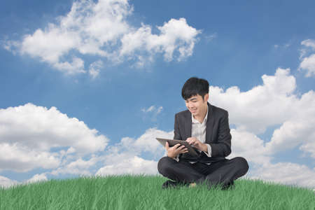 Asian businessman sit and using pad in outdoor. photo