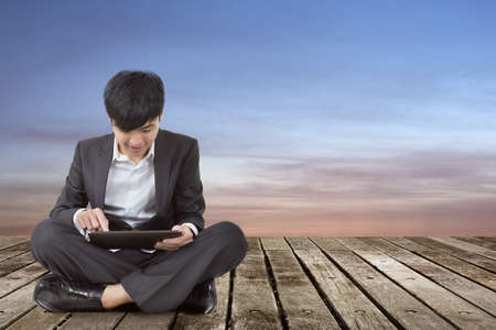 Asian business man using pad and sit on ground. photo