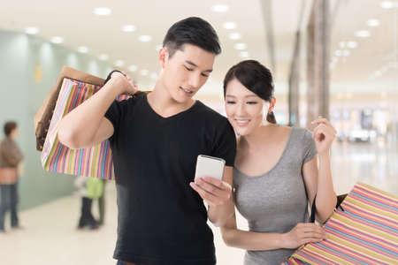 若いアジアのカップル ショッピングや携帯電話、クローズ アップの肖像画を見てします。 写真素材