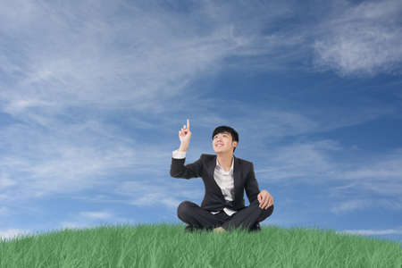 Businessman sit on grassland and finger toward the sky. photo
