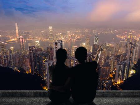 부부의 실루엣 밤에 도시 위의 지붕에 접지 포인트 먼에 앉아있다. 스톡 콘텐츠