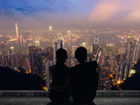 in distance: Silhouette of couple sit on ground point faraway on the roof above the city in the night. Stock Photo