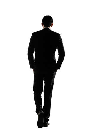 Silhouette of Asian business man walk with confidence, full length portrait isolated on white. Rear view. Standard-Bild