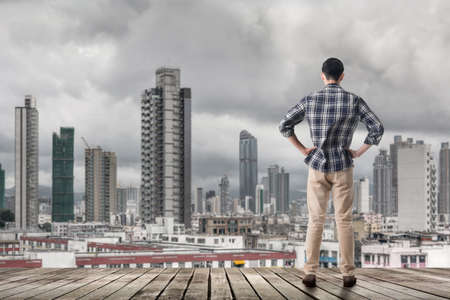 Asian man standing and looking the skyline of the city, Hong kong, Asia. photo