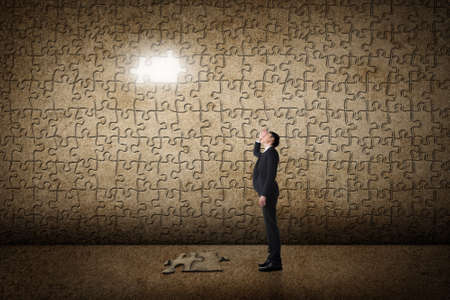 business solutions: Asian man standing in front of a puzzle wall. Concept of mystery, problem, solution. Stock Photo