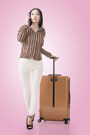 Modern Asian woman talking on cellphone and walking and holding a suitcase. photo