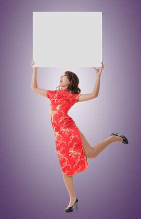 Attractive Chinese woman dress traditional cheongsam and hold blank board, full length portrait. photo