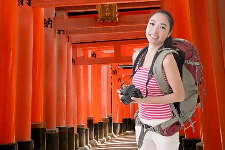 sightsee: Happy smiling Asian young female backpacker with camera in Fushimi Inari Taisha, Japan. Stock Photo
