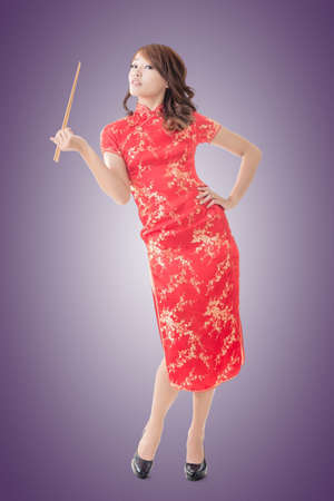 Smiling Chinese woman dress traditional cheongsam standing and holding chopsticks at New Year, full length portrait  isolated. photo