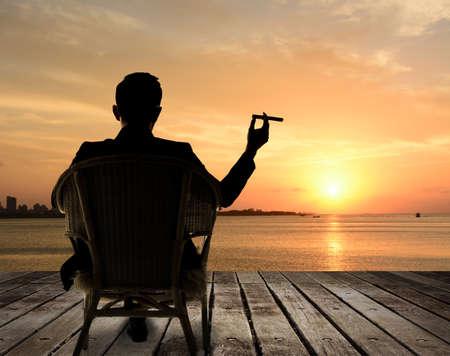 cigarro: Silueta de hombre de negocios se sienta en silla y mantenga un cigarro y mirando a la ciudad en la noche.