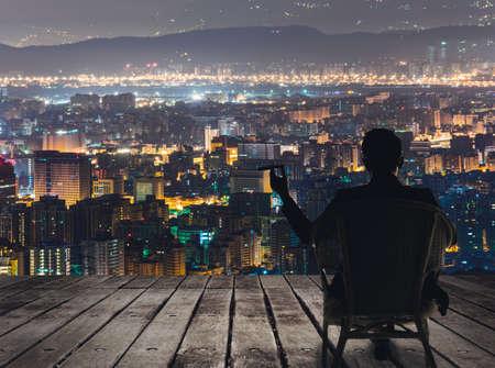 företag: Silhuett av affärsman sitta på stolen och håller en cigarr och tittar på staden i natten.