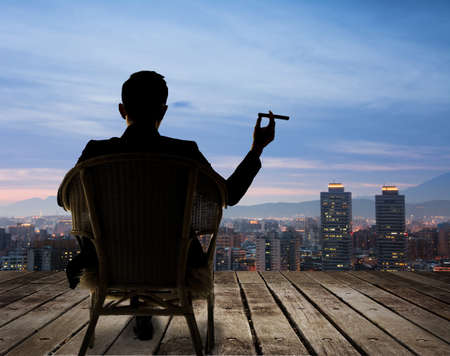 사업가의 실루엣 의자에 앉아 길게 시가와 밤에 도시를 찾고 있습니다.