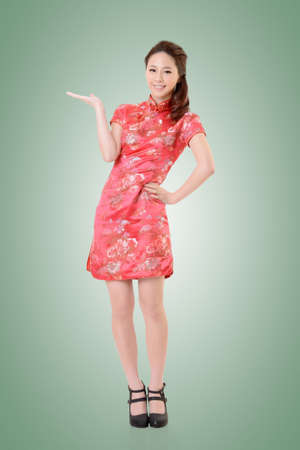 Smiling Chinese woman dress traditional cheongsam and introduce. photo