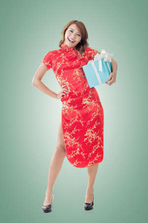 Smiling Chinese woman dress traditional cheongsam standing and holding a gift box at New Year, full length portrait  isolated. photo