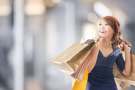 Veselá nákupní žena asijských drží tašky.