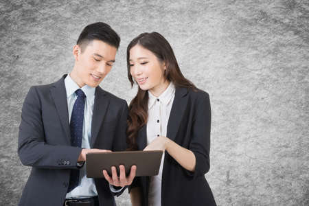 office staff: Business man and woman hold a tablet and discuss, closeup portrait with copyspace.