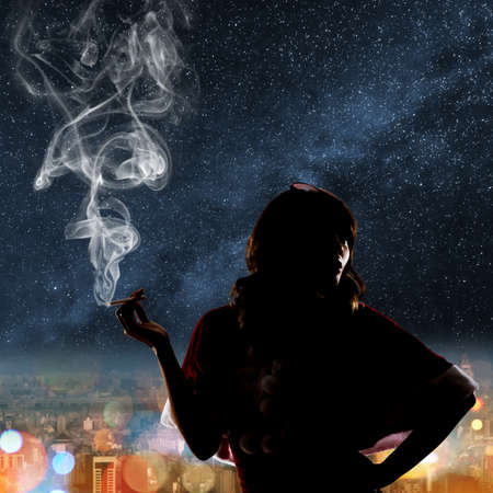 sexy xmas elf: Silhouette of Asian christmas girl holding a cigar in the city night. Stock Photo