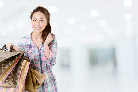 closeup on bags: Exciting young shopping woman hold bags, closeup portrait with copyspace.