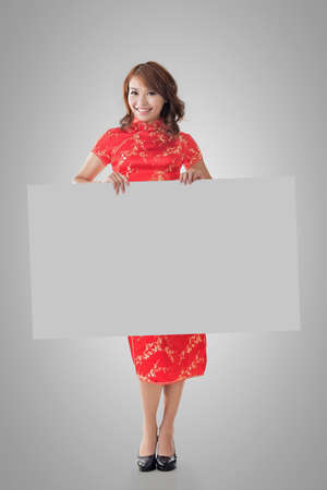 instruction sheet: Attractive Chinese woman dress traditional cheongsam and hold blank board, full length portrait.