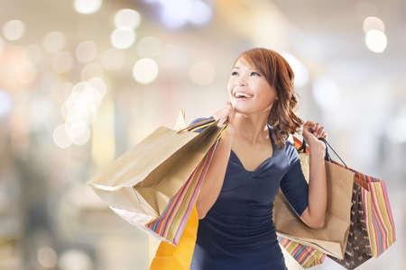 アジアの保持袋の陽気なショッピング女性。 写真素材
