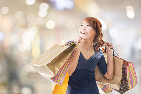 excited: Cheerful shopping woman of Asian holding bags. Stock Photo