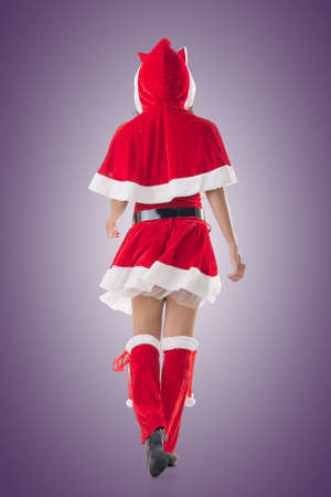 mrs  claus: Asian Christmas girl walk, full length portrait. Rear view. Stock Photo