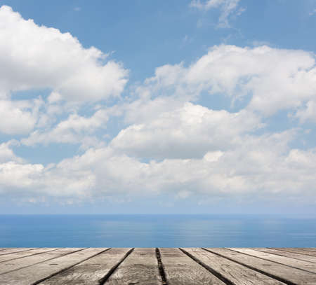 wooden deck: Empty wooden deck table with copyspace under sunny cloudy sky in the beach, focus on the wooden ground.