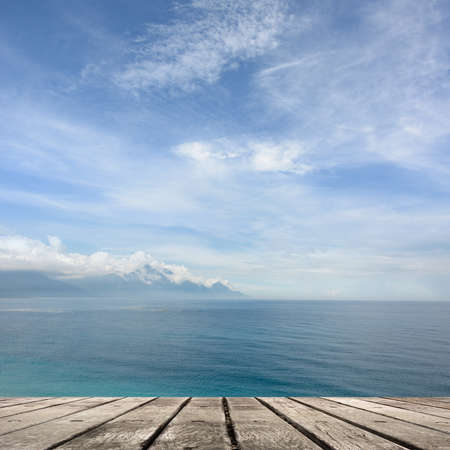 heave: Empty wooden deck table with copyspace under sunny cloudy sky in the beach, focus on the wooden ground.