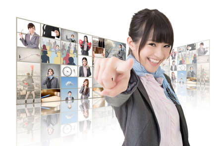 tv wall: Confident Asian business woman point at you standing in front of TV screen wall, closeup portrait. Stock Photo