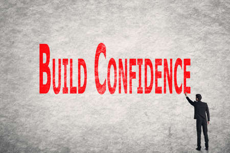 self assurance: Asian business man write words on wall, Build Confidence Stock Photo