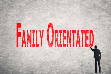 orientated: Asian business man write words on wall, Family Orientated Stock Photo