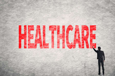 mandated: Asian business man write words on wall, Healthcare