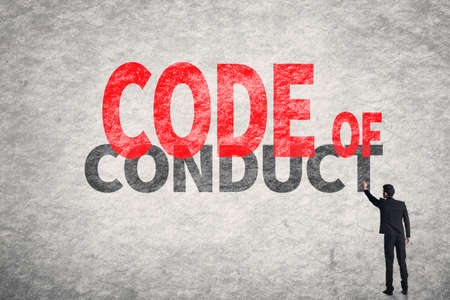 work ethic responsibilities: Asian business man write words on wall, Code Of Conduct Stock Photo
