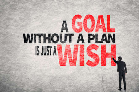 metas: Asia palabras del hombre de negocios de escritura en la pared, un objetivo sin un plan es s�lo un deseo Foto de archivo