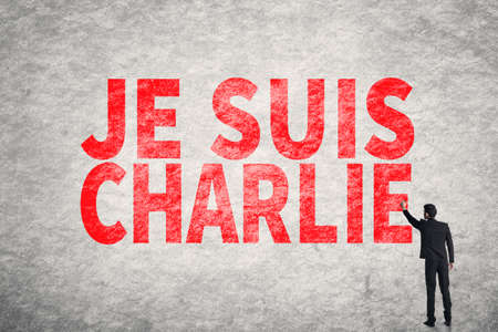 massacre: Asian businessman write text on wall, I am Charlie (In French) Stock Photo