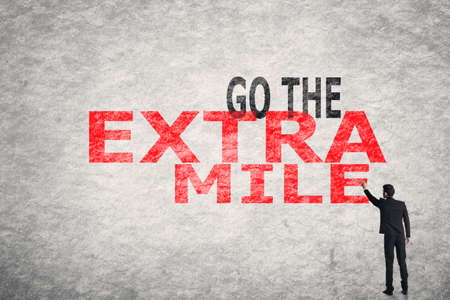 perseverance: Asian businessman write text on wall, Go To Extra Mile