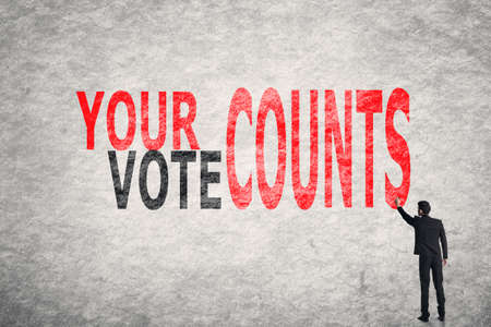 election debate: Asian businessman write text on wall, Your Vote Counts