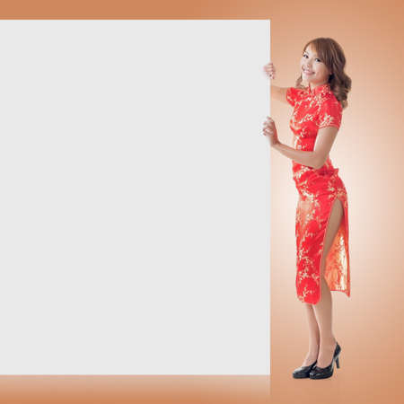 qipao: Attractive Chinese woman dress traditional cheongsam and hold blank board, full length portrait.