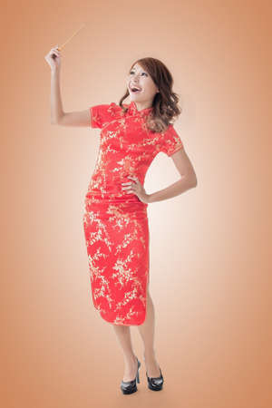 qipao: Smiling Chinese woman dress traditional cheongsam standing and holding chopsticks at New Year, full length portrait  isolated.
