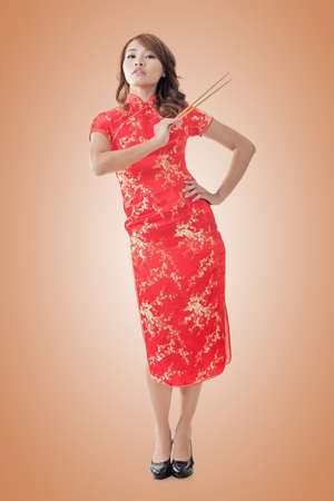 chipao: Smiling Chinese woman dress traditional cheongsam standing and holding chopsticks at New Year, full length portrait  isolated.
