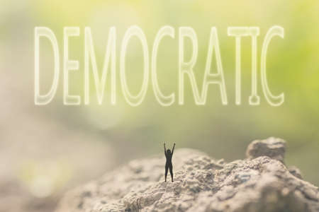 elect: Concept of democracy with a person stand in the outdoor and looking up the text over the sky in nature background.