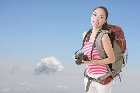 avocation: Happy smiling Asian young female backpacker with camera standing in front of blue sky.