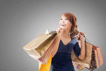 cara sorprendida: Compras de la mujer alegre de celebración de las bolsas asiáticas. Foto de archivo