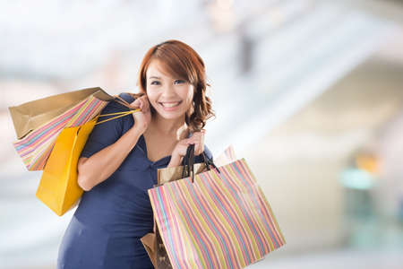 korean woman: Cheerful shopping woman of Asian holding bags. Stock Photo