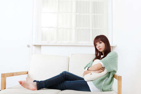 Young Asian woman sit on sofa in home with lonely expression on face. photo