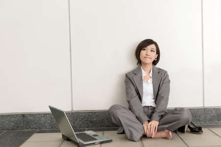 Asian young business woman take off her shoes and relax sitting on ground in modern building. Stock Photo