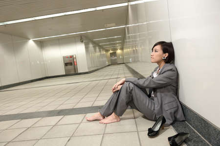 shoes off: Asian young business woman take off her shoes and relax sitting on ground in modern building. Stock Photo