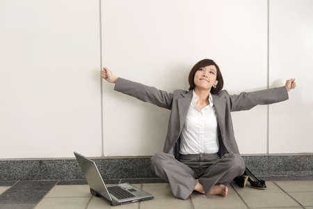 sitting on the ground: Asian young business woman take off her shoes and relax sitting on ground in modern building. Stock Photo