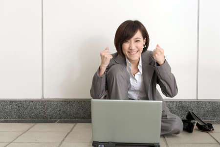 sitting on the ground: Cheerful business woman sitting and using laptop on ground. Stock Photo
