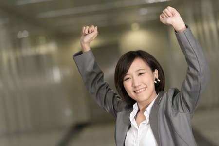 winning business woman: Cheerful and exciting business woman of Asian inside of modern buildings.